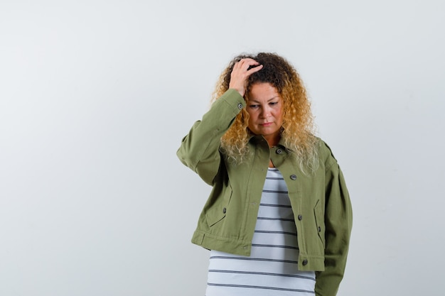 Mature woman holding hand on head, looking down in green jacket, t-shirt and looking upset , front view.
