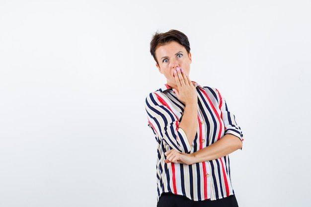 Mature woman holding hand on mouth in striped shirt and looking surprised , front view.