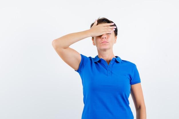 파란색 티셔츠에 이마에 손을 잡고 잠겨있는 찾고 성숙한 여자. 전면보기.