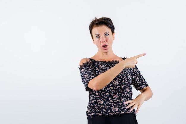 人差し指で右を指して、腰に手を持っている成熟した女性
