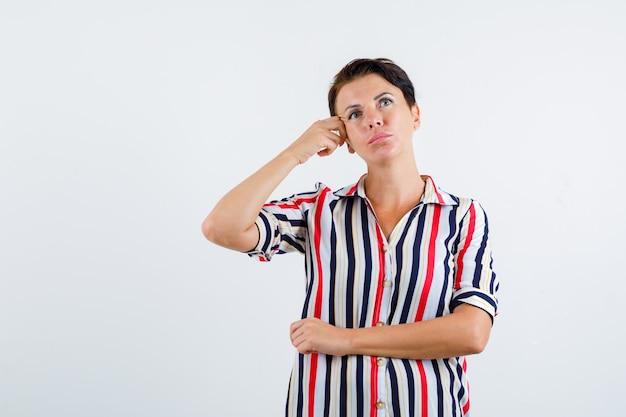 Donna matura che tiene la mano sul tempio, pensando a qualcosa in camicetta a righe e guardando pensieroso, vista frontale.
