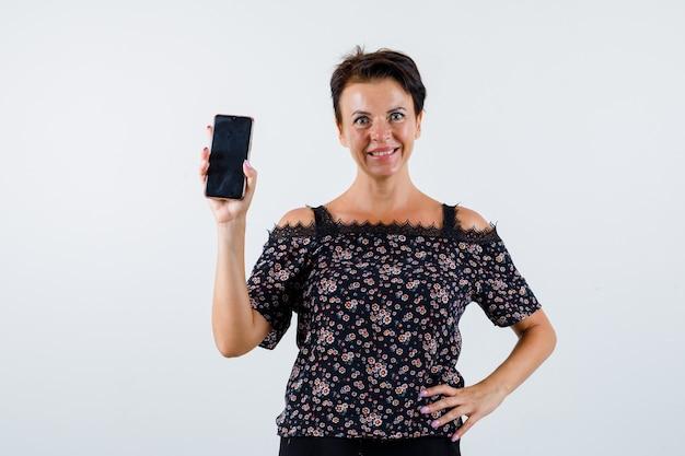 Donna matura che tiene la mano sulla vita, mostrando il telefono in camicetta floreale, gonna nera e guardando fiducioso, vista frontale.