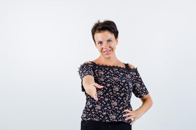 Donna matura che tiene la mano sulla vita, allungando la mano per salutare in camicetta floreale, gonna nera e aspetto amabile. vista frontale.