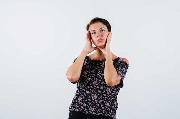 Donna matura che tiene le mani sulle guance in camicetta floreale, gonna nera e sembra affascinante. vista frontale.