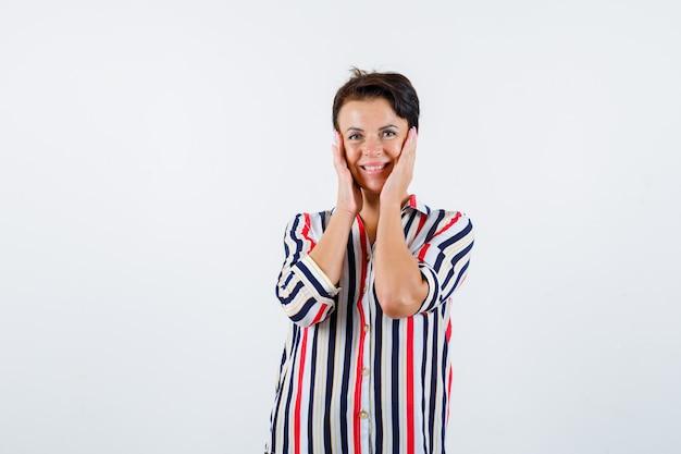 Donna matura che tiene le mani sulle guance in camicetta a righe e sembra allegro. vista frontale.