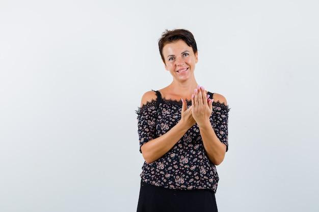 Donna matura che tiene le mani davanti a lei in camicetta floreale e gonna nera e sembra allegra, vista frontale.