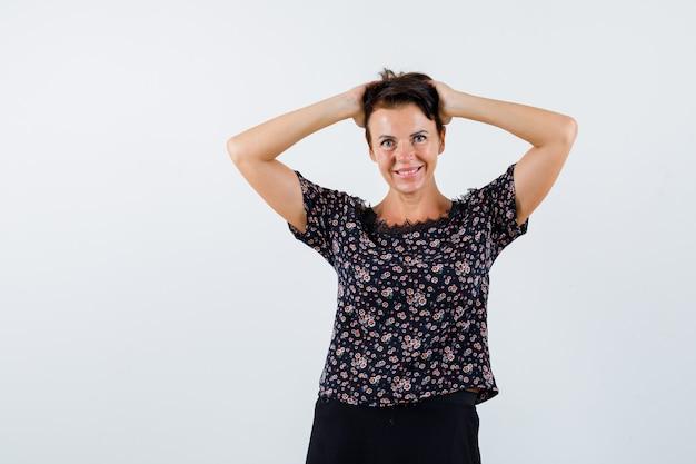 Donna matura che tiene le mani sulla testa in camicetta floreale e gonna nera e sembra allegra. vista frontale.