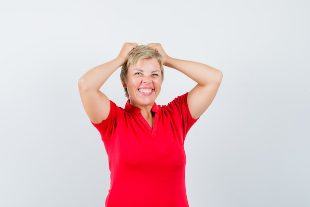 Mature woman holding hands on head in red t-shirt and looking forgetful.