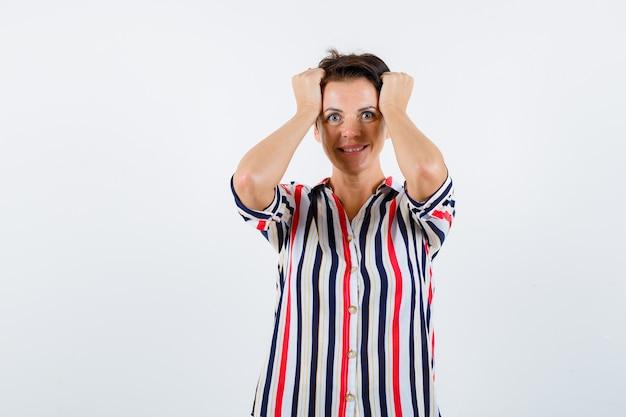 Donna matura che tiene le mani sulla testa, sorridendo in camicetta a righe e guardando vivace. vista frontale.