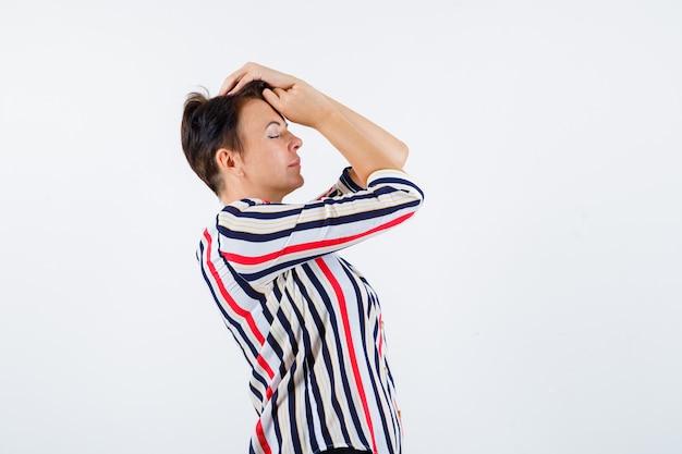 Donna matura che tiene le mani sulla testa in camicetta a righe e che sembra calma. vista frontale.
