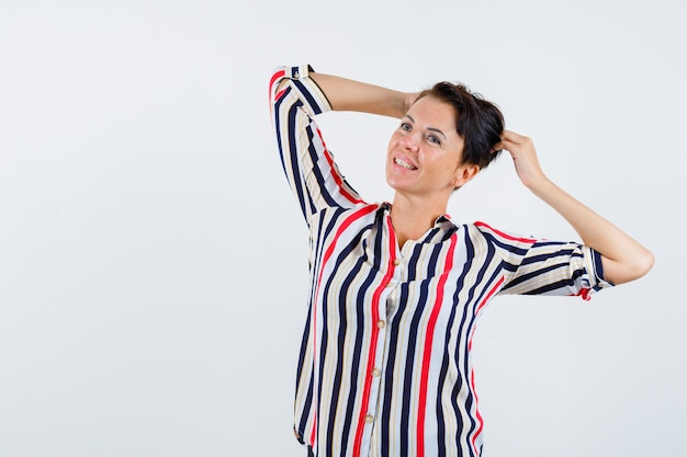 Donna matura che tiene le mani sulla testa in camicetta a strisce e che sembra allegra. vista frontale.