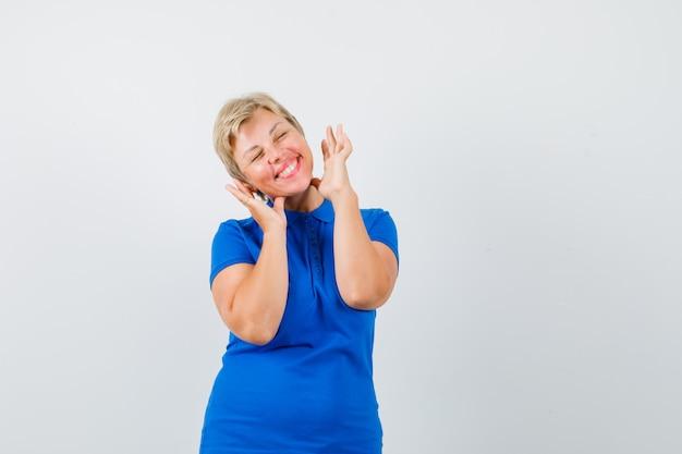 Tシャツで顔の近くで手をつないで嬉しそうに見える成熟した女性。