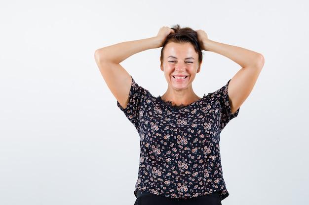 頭に手をつないで、花柄のブラウス、黒いスカートに笑みを浮かべて、陽気に見える成熟した女性。正面図。
