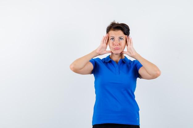 青いtシャツで顔の側面に手をつないで物思いにふける成熟した女性。正面図。