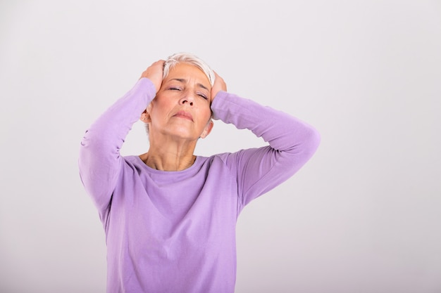 Зрелая женщина, держа голову руками, имея головную боль и плохо себя чувствует. старший женщина с головной болью, выражение лица боли.