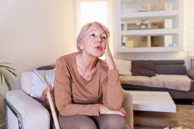 Зрелая женщина, держа голову руками, имея головную боль и плохо себя чувствует.
