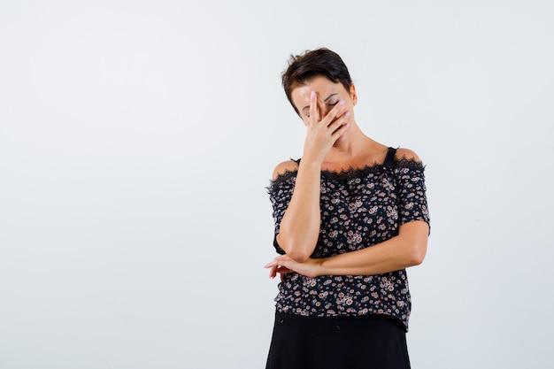 Зрелая женщина держит одну руку на лице, другую руку под локтем в блузке с цветочным рисунком и черной юбке и выглядит усталой. передний план.