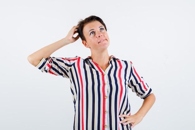 片方の手を頭に、もう片方の手を腰にストライプのシャツを着て物思いにふける成熟した女性。正面図。