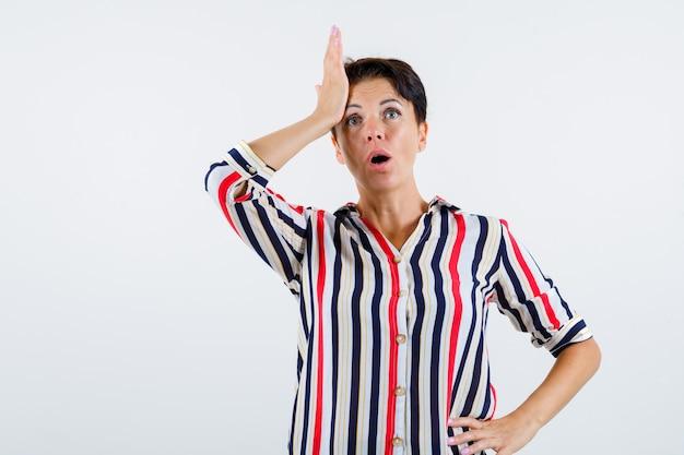 片方の手を寺院に、もう片方の手を腰に縞模様のシャツを着て、驚いて見える成熟した女性、正面図。