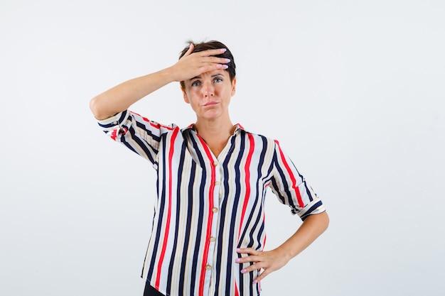 성숙한 여인은 허리에 한 손을 잡고, 스트라이프 셔츠에 이마에 다른 손을 잡고 해리 된, 전면보기를 찾고 있습니다.