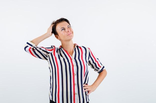 片方の手を腰に、もう片方の手を頭に抱え、縞模様のシャツを着て何かを考え、物思いにふける成熟した女性。正面図。