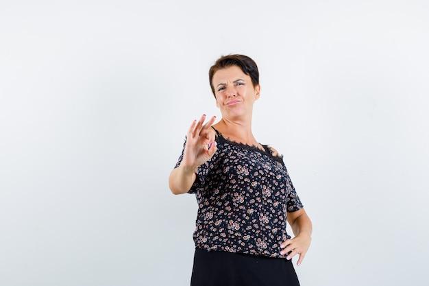 Donna matura che tiene una mano sulla vita, che mostra il segno giusto in camicetta floreale e gonna nera e sembra sicura. vista frontale.