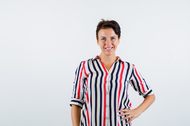 Mature woman holding one hand on waist, smiling in striped shirt and looking charming. front view.