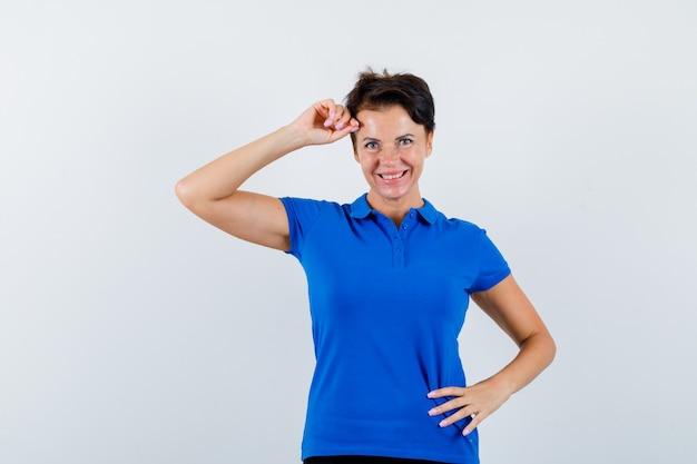青いtシャツを着て頭に手を上げて自信を持って見える成熟した女性。正面図。
