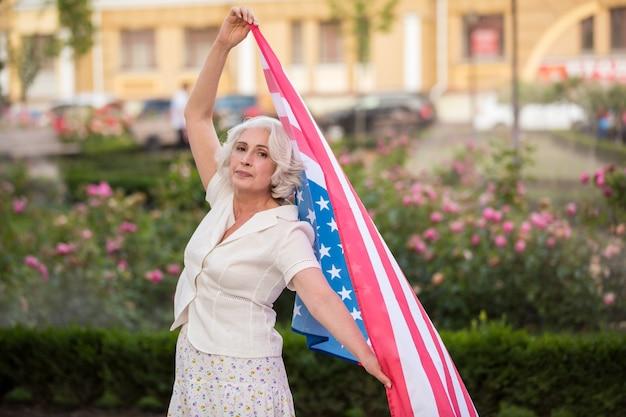 성숙한 여자는 미국 국기를 보유하고 있습니다.