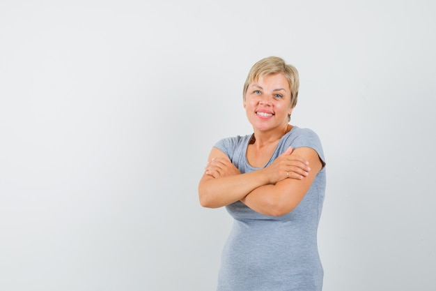 Mature woman hugging herself in grey t-shirt and looking cute.