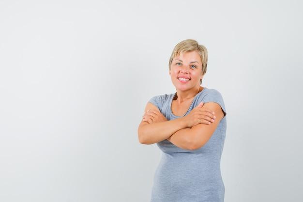Зрелая женщина обнимает себя в серой футболке и выглядит мило.