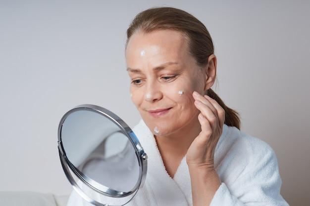 鏡を見ている白い朝のガウンの成熟した女性。古い肌のためのホームスキンケア。