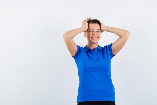 手に頭を握りしめ、平和な正面図を探している青いtシャツの成熟した女性。