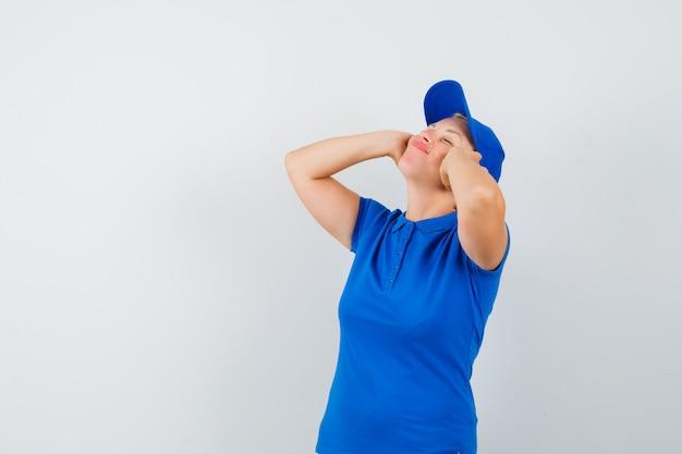 耳に手をつないで平和に見える青いtシャツの成熟した女性。