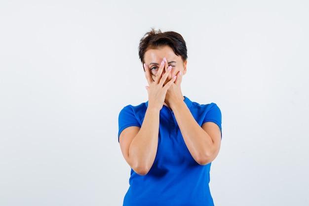 指を通して見て、好奇心旺盛な、正面図を見て青いtシャツの成熟した女性。