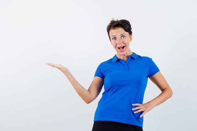 歓迎のジェスチャーをし、驚いて見える青いtシャツの成熟した女性、正面図。