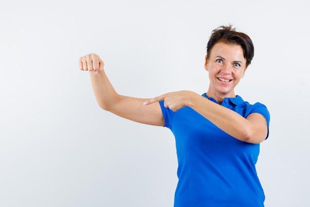 腕の筋肉を指して、誇らしげに見える青いtシャツの成熟した女性、正面図。