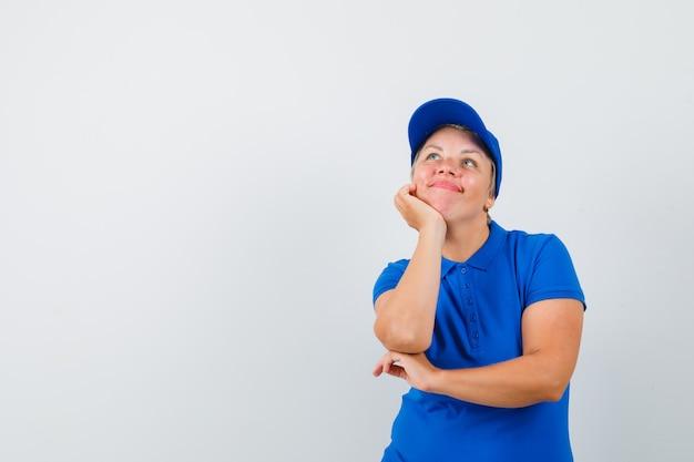 턱 손에지지하고 꿈꾸는 찾고 파란색 티셔츠에 성숙한 여자.