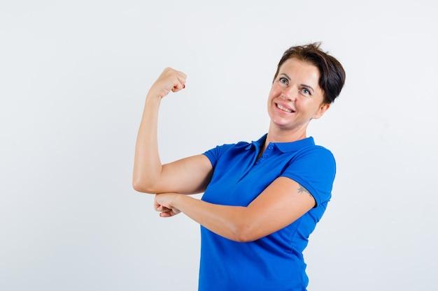 腕の筋肉を示し、自信を持って、正面図を示す青いtシャツの成熟した女性。