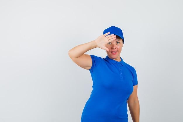 Зрелая женщина в синей футболке показывает ладонь, чтобы попрощаться