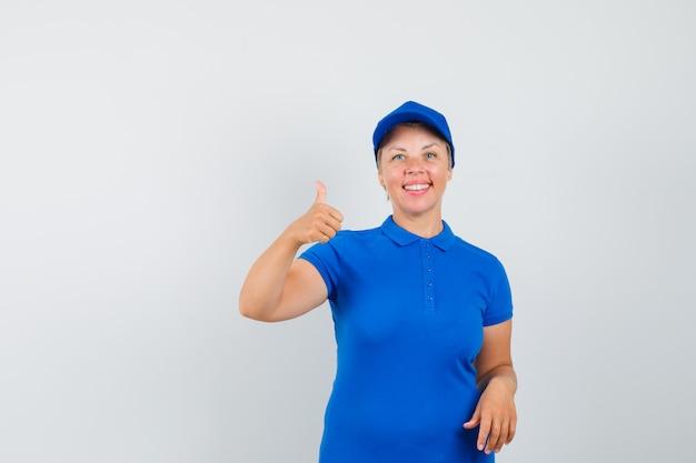 親指を立てて楽観的に見える青いtシャツの成熟した女性