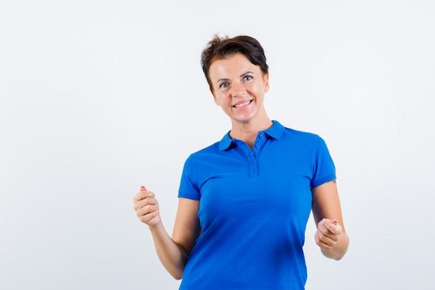 승자 제스처를 표시 하 고 기쁜, 전면보기를 찾고 파란색 티셔츠에 성숙한 여자.