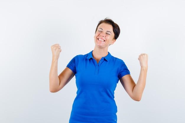 승자 제스처를 표시하고 운이 좋은, 전면보기를 찾고 파란색 티셔츠에 성숙한 여자.