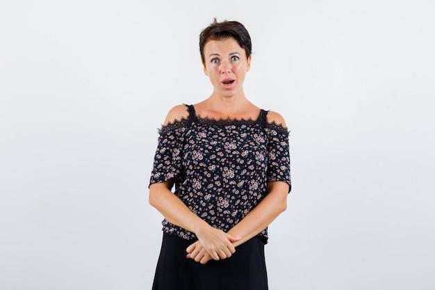 花柄のブラウスと黒いスカートの成熟した女性が彼女の前で手をつないで、口を大きく開いたままにして驚いたように見える、正面図。