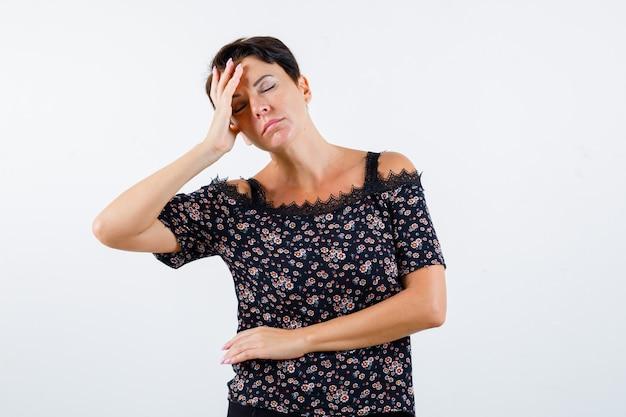 花柄のブラウス、頭痛があり、疲れ果てているように見える黒いスカートの成熟した女性、正面図。