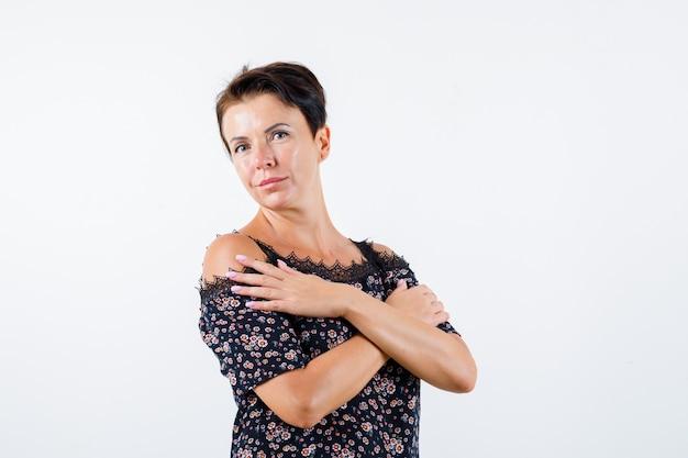 Зрелая женщина в цветочной блузке, черной юбке держит две руки, скрещенные на груди, и выглядит очаровательно, вид спереди.