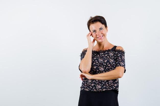 Зрелая женщина в блузке с цветочным рисунком, черная юбка, опираясь щекой на ладонь, держа руку под локтем и выглядя очаровательно, вид спереди.