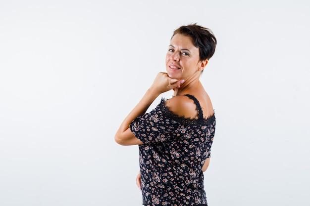 꽃 블라우스에 성숙한 여인, 손에 턱을지지하는 검은 치마, 어깨 너머로보고 매력적인, 전면보기.
