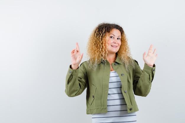 녹색 재킷에 성숙한 여인, t- 셔츠 유지 손가락 교차 및 긍정적, 전면보기.