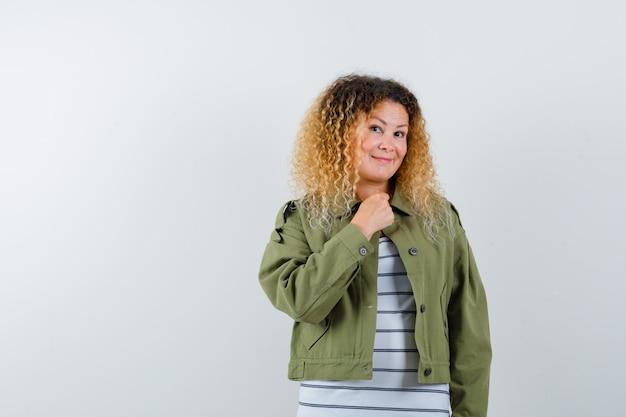 緑のジャケット、胸に手を保ち、陽気に見えるtシャツ、正面図の成熟した女性。